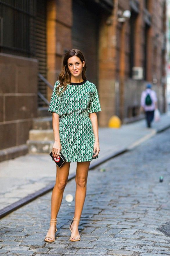 Amlul in a green patterned dress paired with black clutch and nude sandals to complete the look.