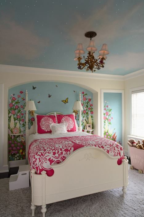 Sky painted on the ceiling. Chandelier. Garden whimsy painted on the walls. Bright bold bedding.
