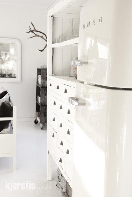 crisp white w/ grey/black toned wood pieces .+ loving the shelving beside the fridge {open top shelves & lots of little drawers .}