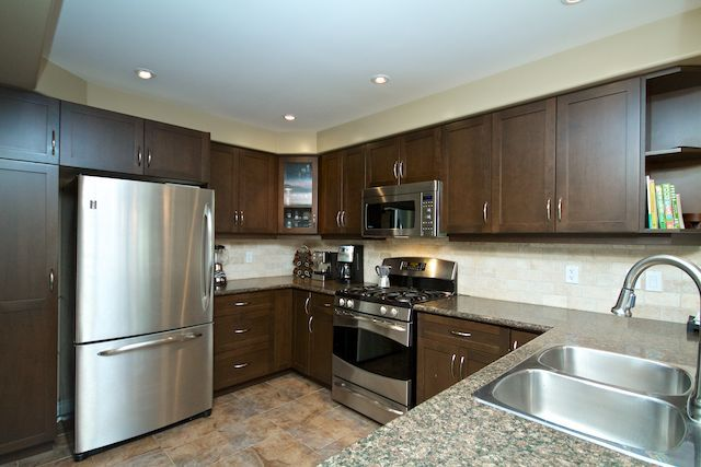 86 Willow Lane Grimsby 449 900 Dark Chocolate Cabinets Tumbled Marble Backsplash Stainless Steel Appliances Rem Kitchen Design Marble Backsplash Cabinet