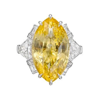 Yellow sapphire ring in a fancy platinum mounting with diamond side stones. Marquise-shaped yellow sapphire weighing 12.46 carats, surrounded by two calf's head-shaped diamonds weighing 1.22 total carats, four baguette-cut diamonds weighing 0.25 total carats and eight round-cut diamonds weighing 0.07 total carats. Designed by Raymond C. Yard