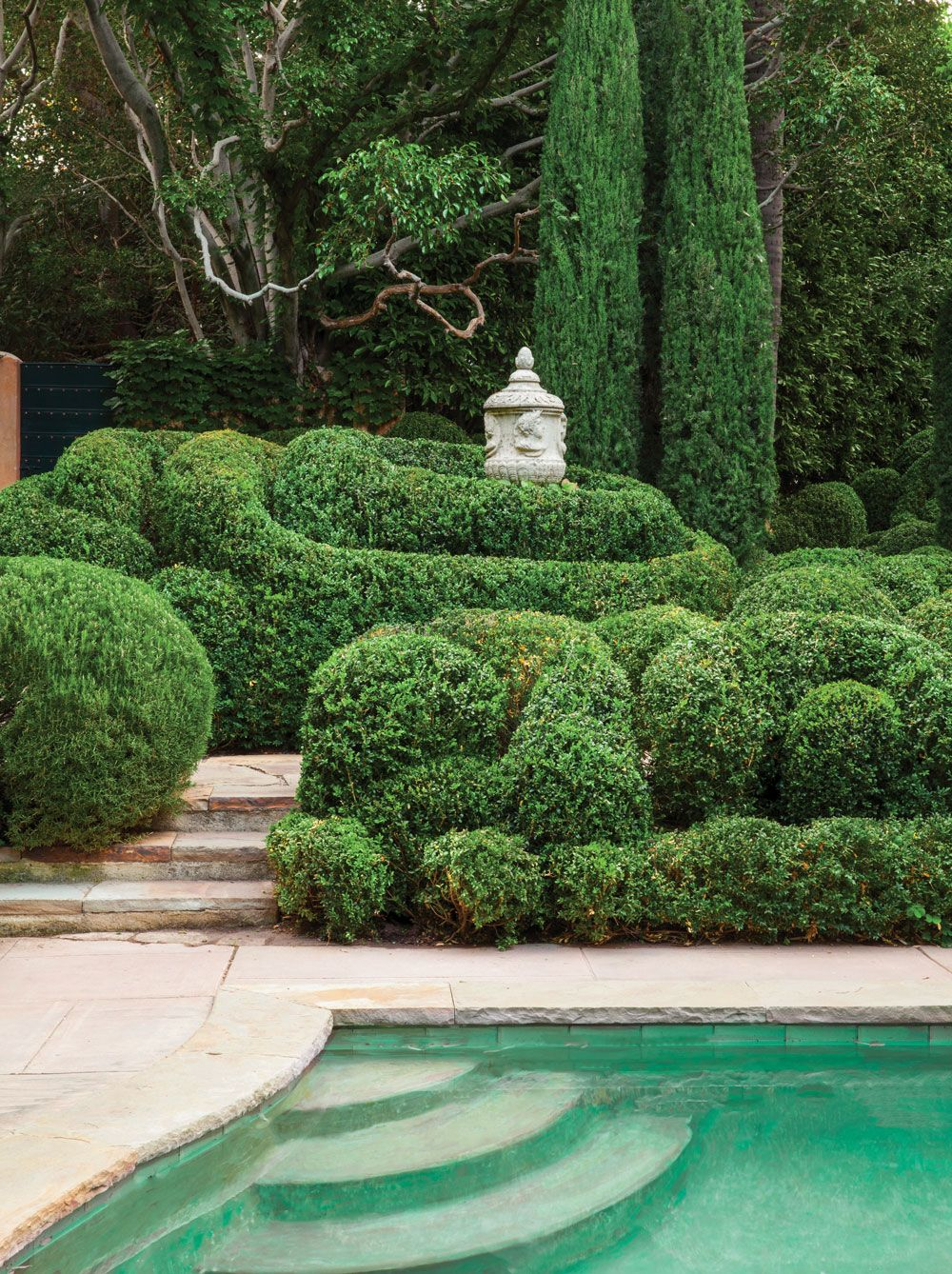 Clouds of trimmed boxwood swirl around an antique italian for Italian pool design 7
