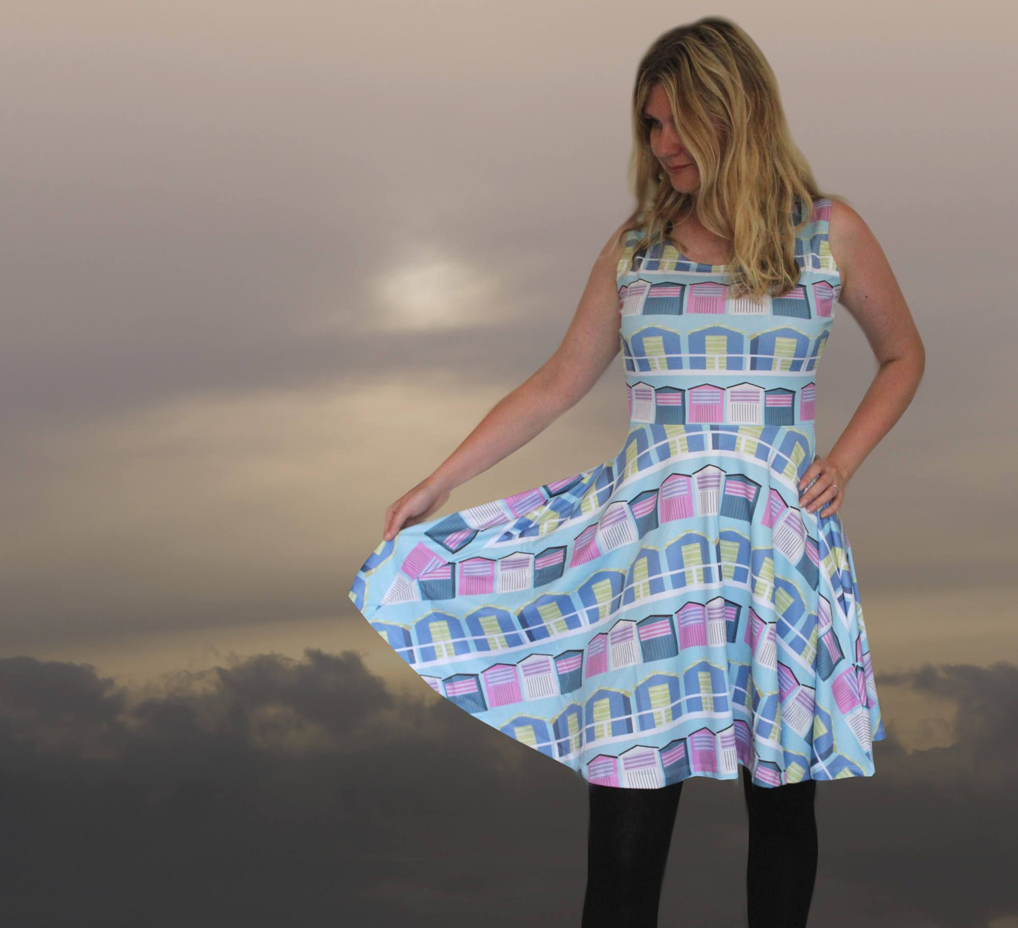 Printed dress with unique summer beach huts print on gorgeous fit flare style.  This flattering dress is designed to hug to the natural waist before flaring out across the hips. The shape is great for taking you through the seasons, accessorised with sunglasses and a wide belt for summer days, or worn with boots and leggings and a cardigan to take you through autumn and into winter. The material has the sheen associated with sublimation printing and a soft feel but is opaque and strong…