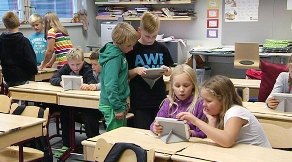 #Väitös: Opettajaa tarvitaan myös oppimispelien aikakaudella  Alakoulualaisia tabletit kädessä luokkahuoneessa.