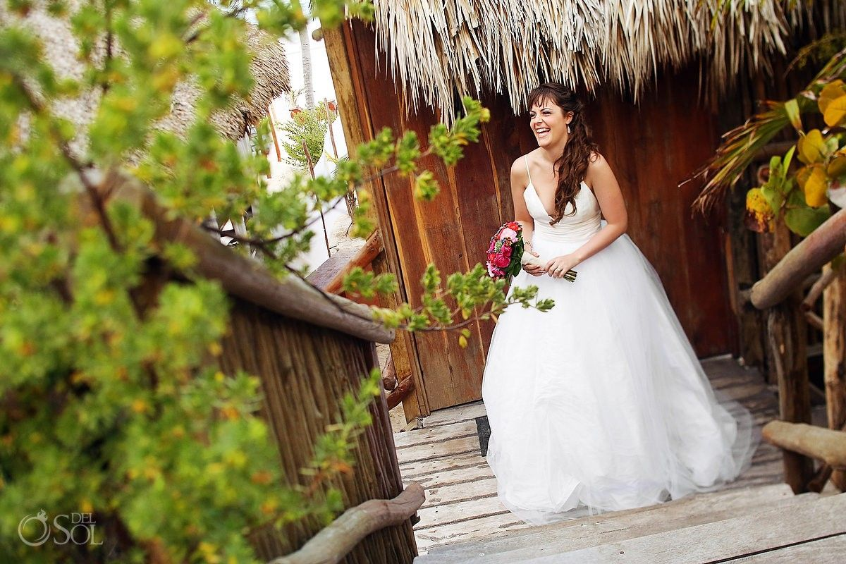 Gorgeus bride with a fabulous smile and pretty pink flowers in a destination wedding at Akiin Beach Club in Tulum. Mexico wedding photographers Del Sol Photography