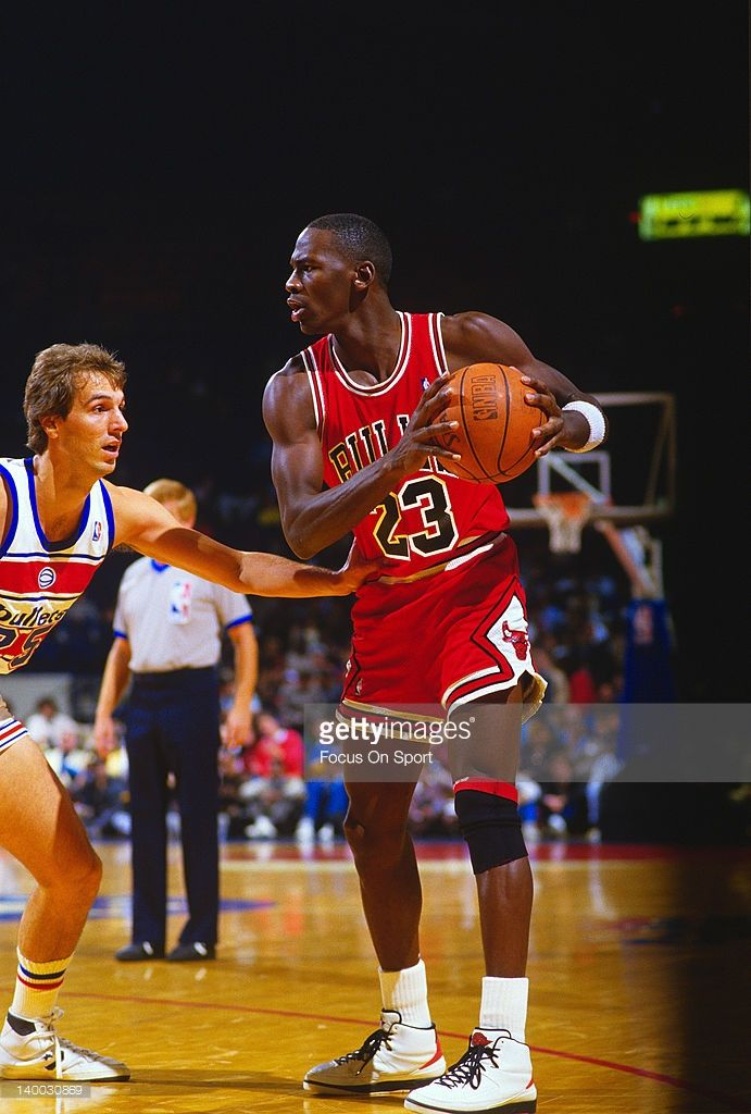 2487f9a2939 Michael Jordan #23 of the Chicago Bulls holding on to the ball is guarded by  Mike O'Koren #25 of the Washington Bullets during an NBA basketball game  circa ...