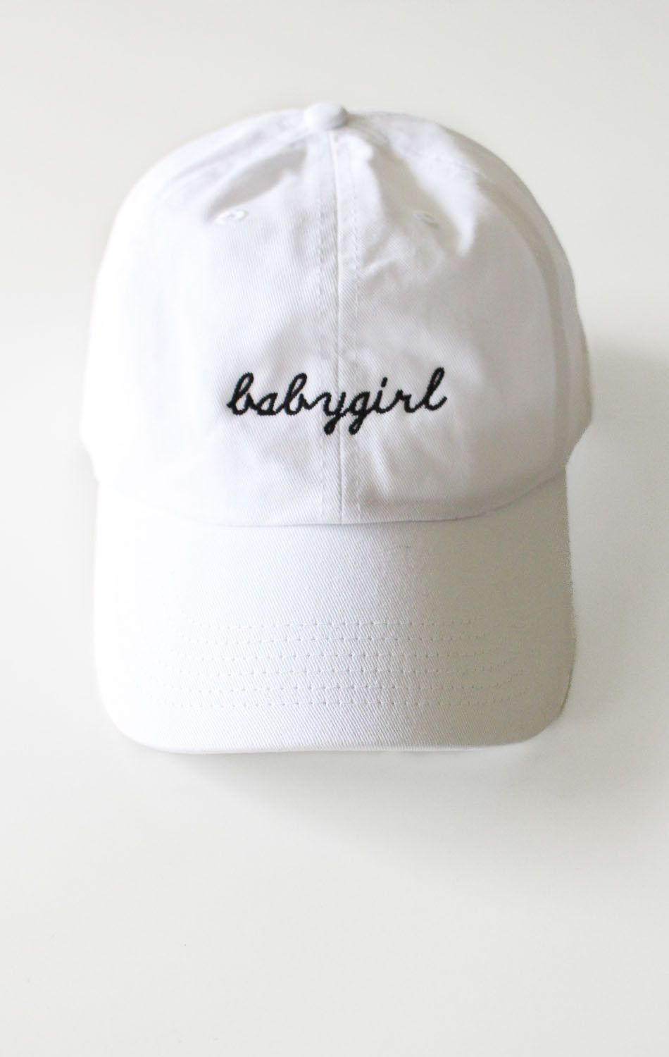 4691ba2a Description Details: White six panel cap with 'babygirl' embroidery &  adjustable back with tri-glide buckle. Brand: NYCT Clothing. 100% Chino  Twill.