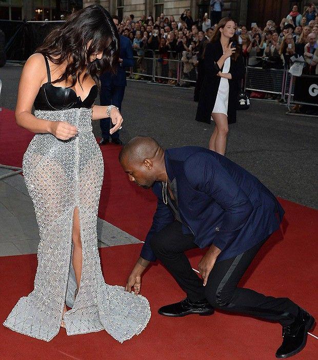 Kanye West ajuda a mulher a arrumar o vestido (Foto: AKM)