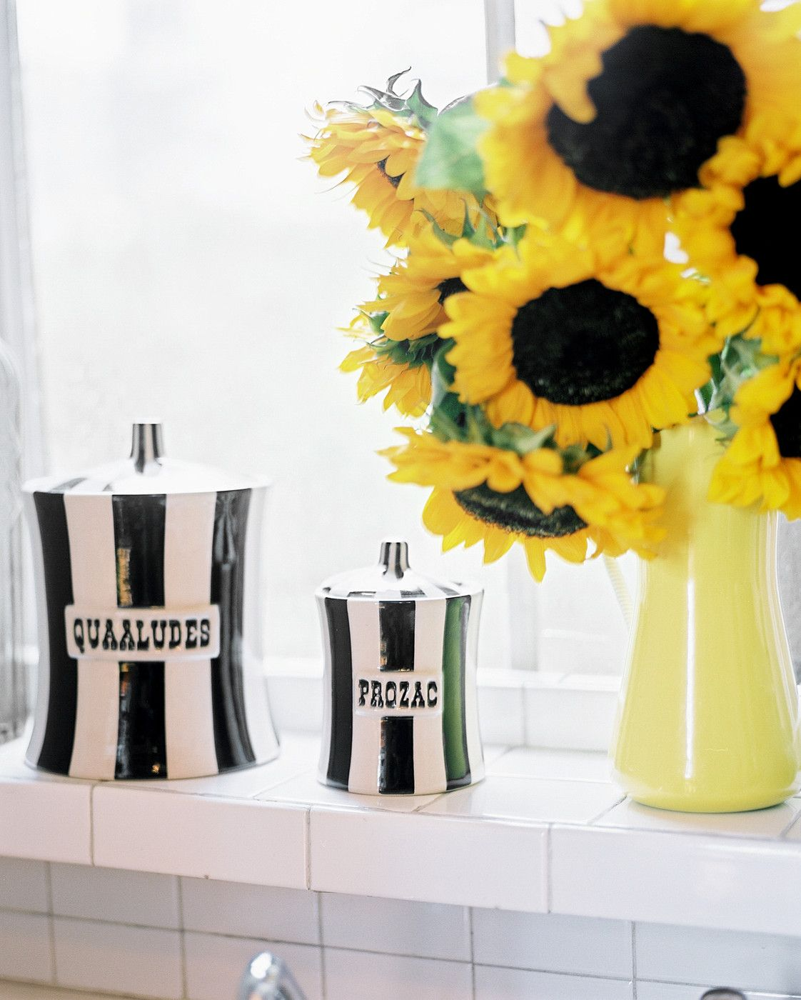 Eclectic Kitchen: Cheeky striped storage containers and a vase of flowers on a shelf covered with white tile.