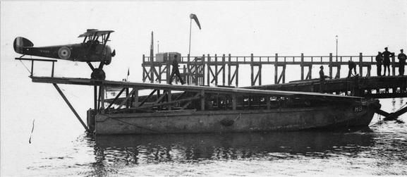 A Sopwith Camel on board a lighter beside the jetty