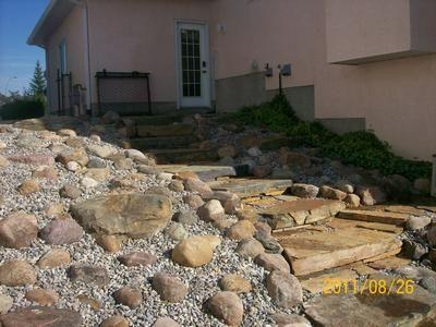 This slope of natural slab steps and a small boulder rock for Sloped rock garden designs