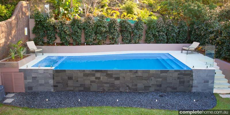 floating blue pool with sandstone paving and glass side | outdoor