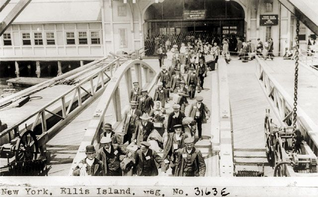 New York. Ellis Island Immigrants walking across pier from bridge ...