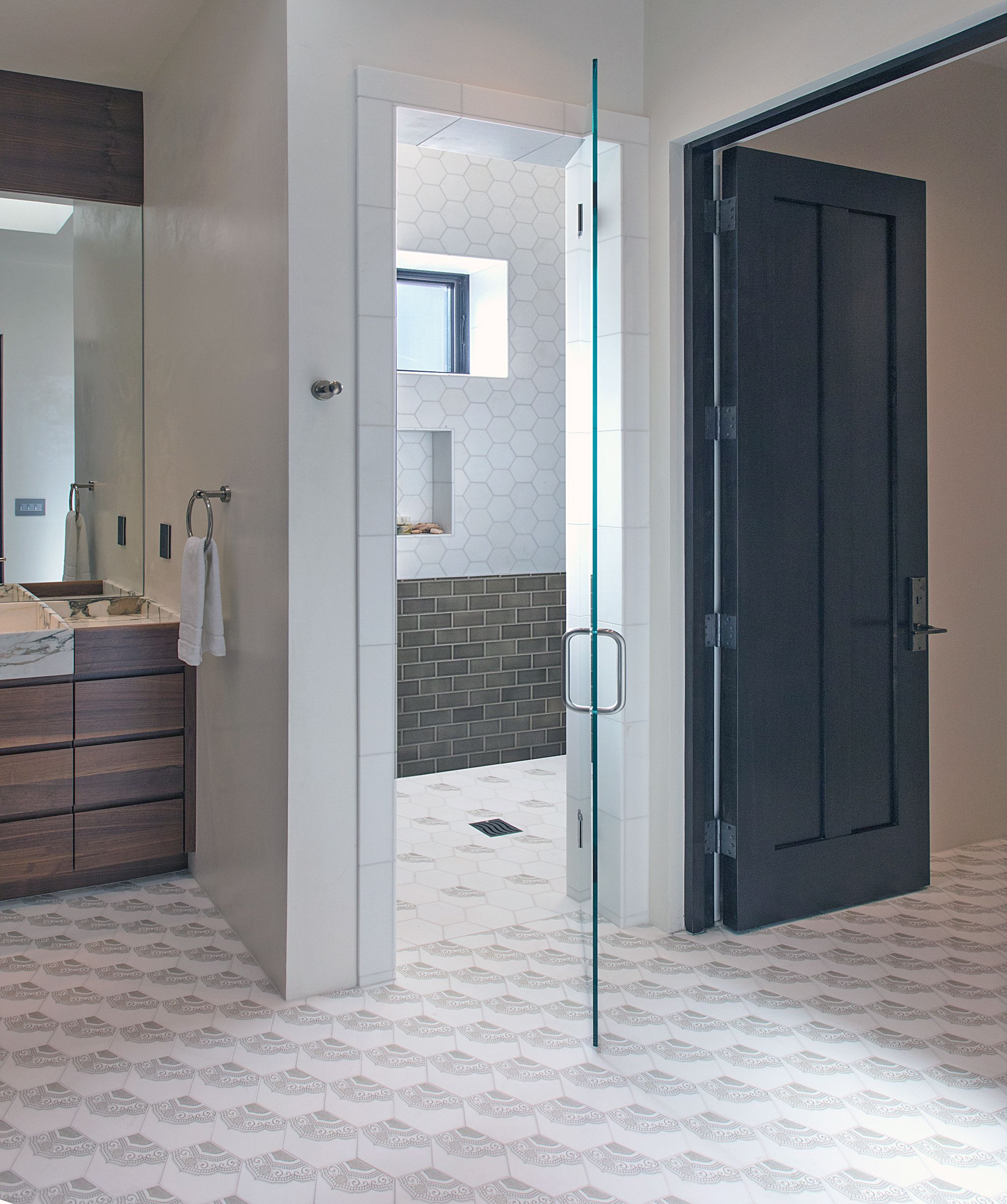 This master bathroom renovation uses our Alston Lola hexagon tile on thassos for the floor and also as a shower niche