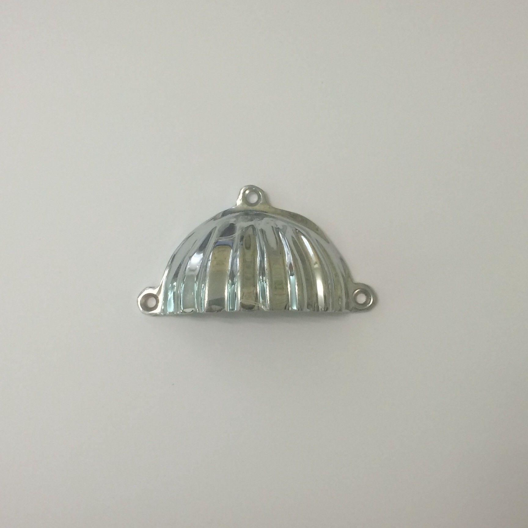 Tirador de asa en forma de concha en cromo brillo.  Medidas aproximadas del tirador: 9 cm. de ancho y 5,5 cm. de alto  Dispone de tres tornillos.
