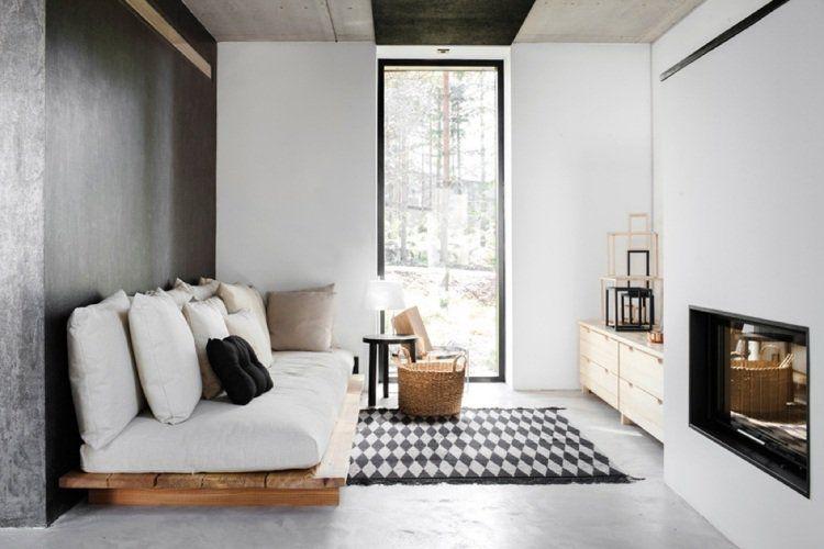 canapé en palette de bois rembouré avec un tapis en noir et blanc
