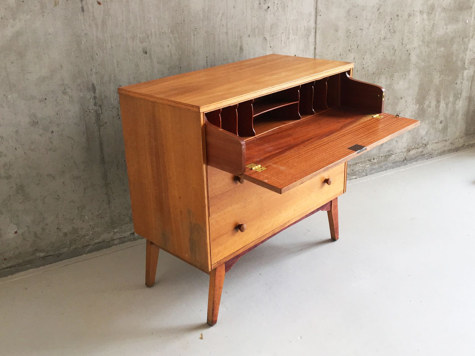This is a teak chest of drawers with a writing desk which