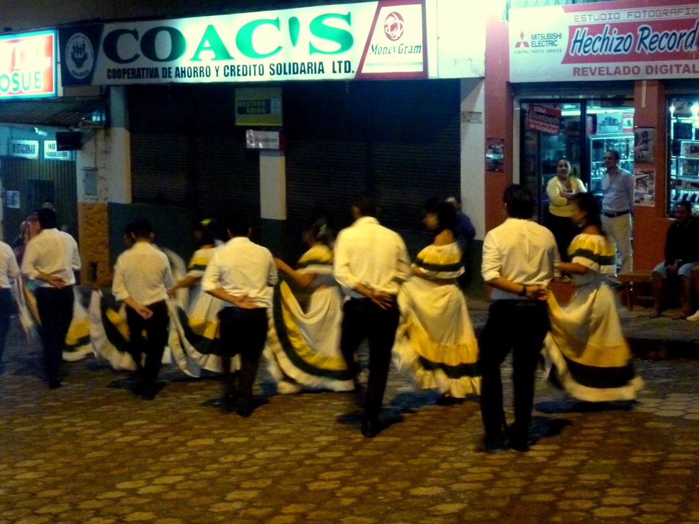 men and women dancing on the street wearing white and black customs