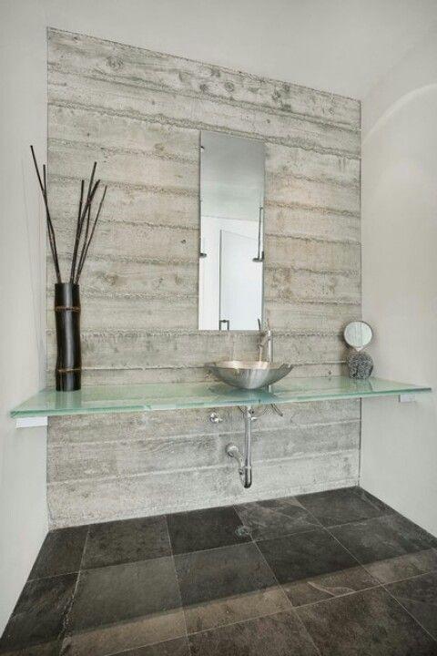 bao con encimera de cristal y lavabo de acero inoxidable en pared de hormign visto
