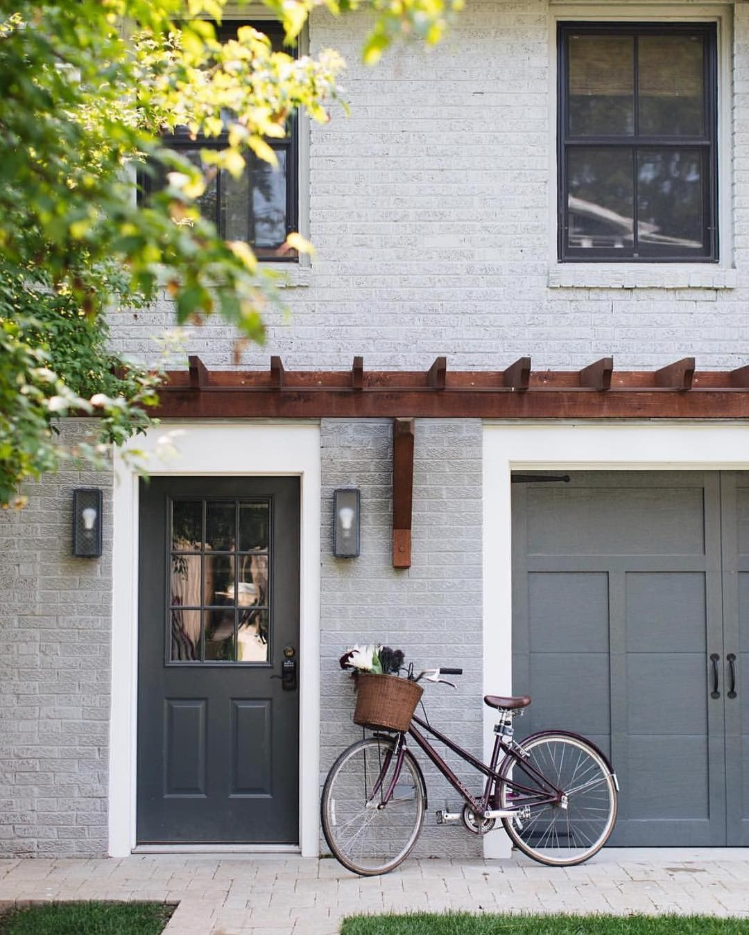 @sketchpadhouseplans posted to Instagram: #blackwindows, #paintedbrick, and a #grey #exterior make this home trendy and cool. Design: @hogankellydesign