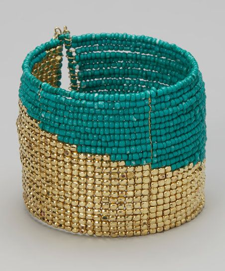 This elegant accessory flaunts a layered look with rows of beautiful beads. Vivid hues engage the eye, while the cuff design is easily slipped on via a flexible opening in back.