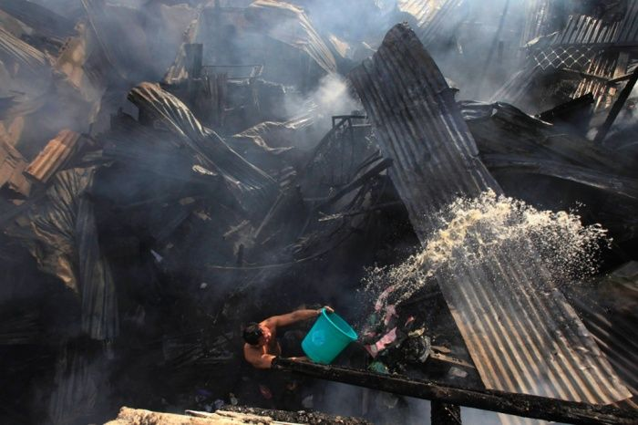 A bucket of water is thrown towards a fire in Manila, Philippines