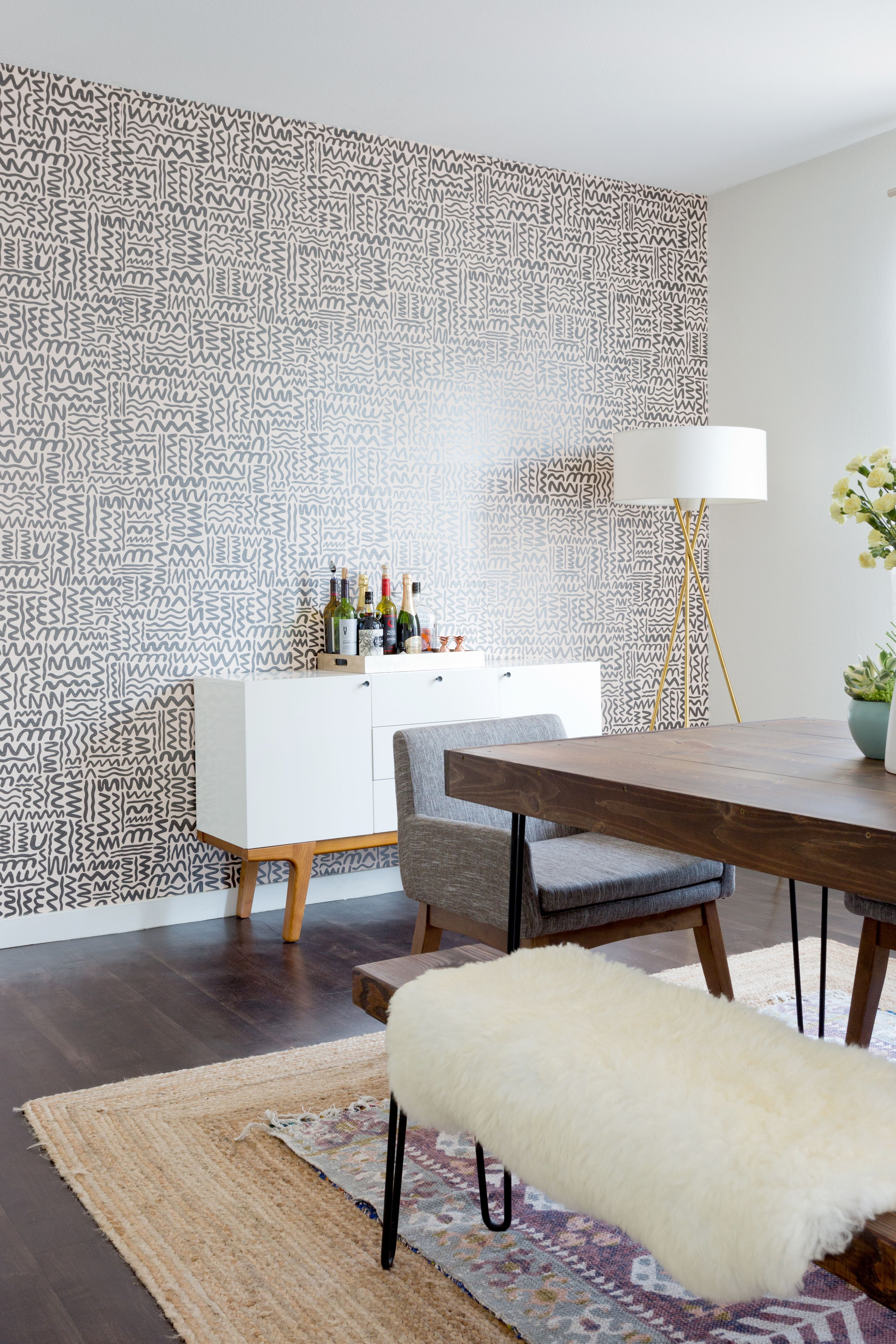 A Dining Room With A Wallpaper Accent Wall And Layered Rugs