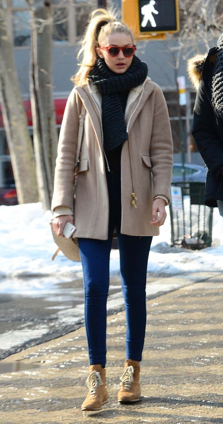 Gigi Hadid street looks - camel coat, skinny jeans, and chunky scarf w/ a high ponytail and red sunglasses