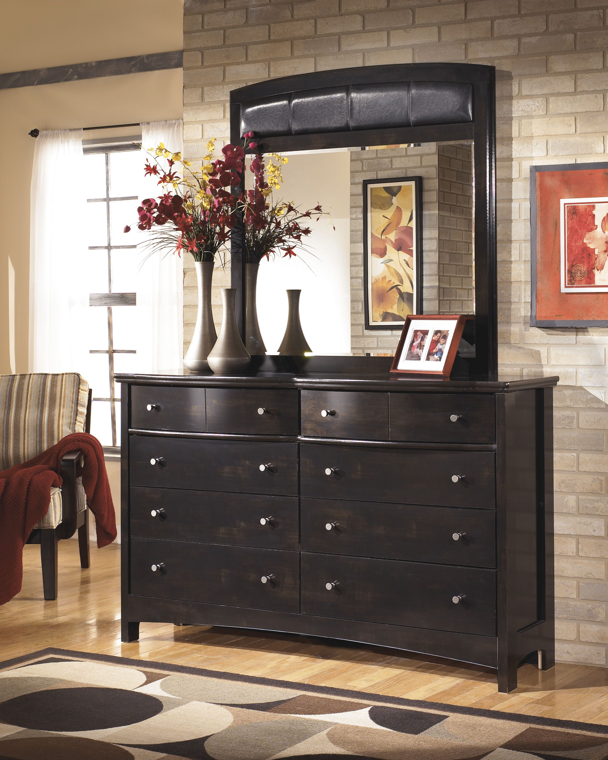 Large scaled dresser has ample storage space and a fauxleather
