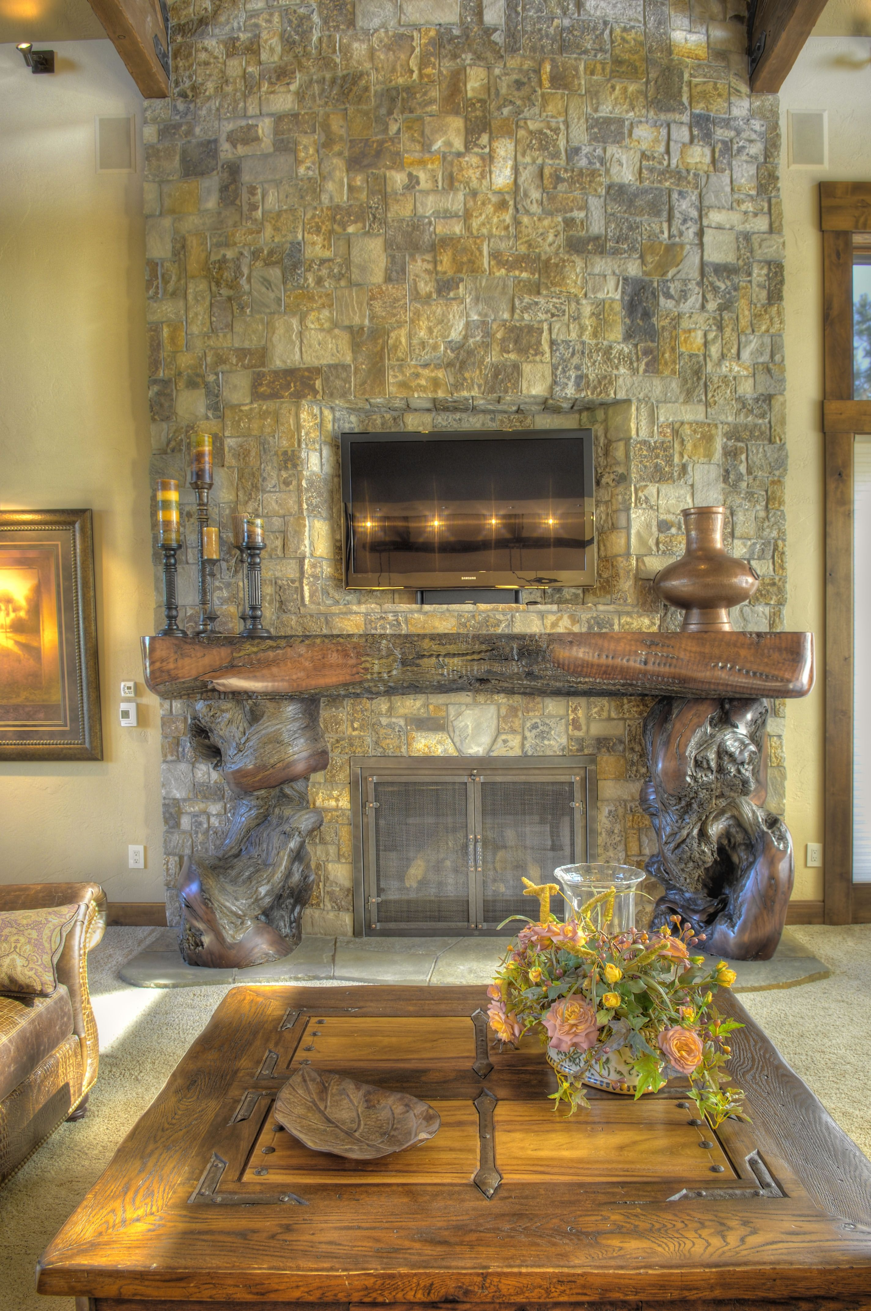 fireplace insert over juniper log mantle on rock fireplace bend or