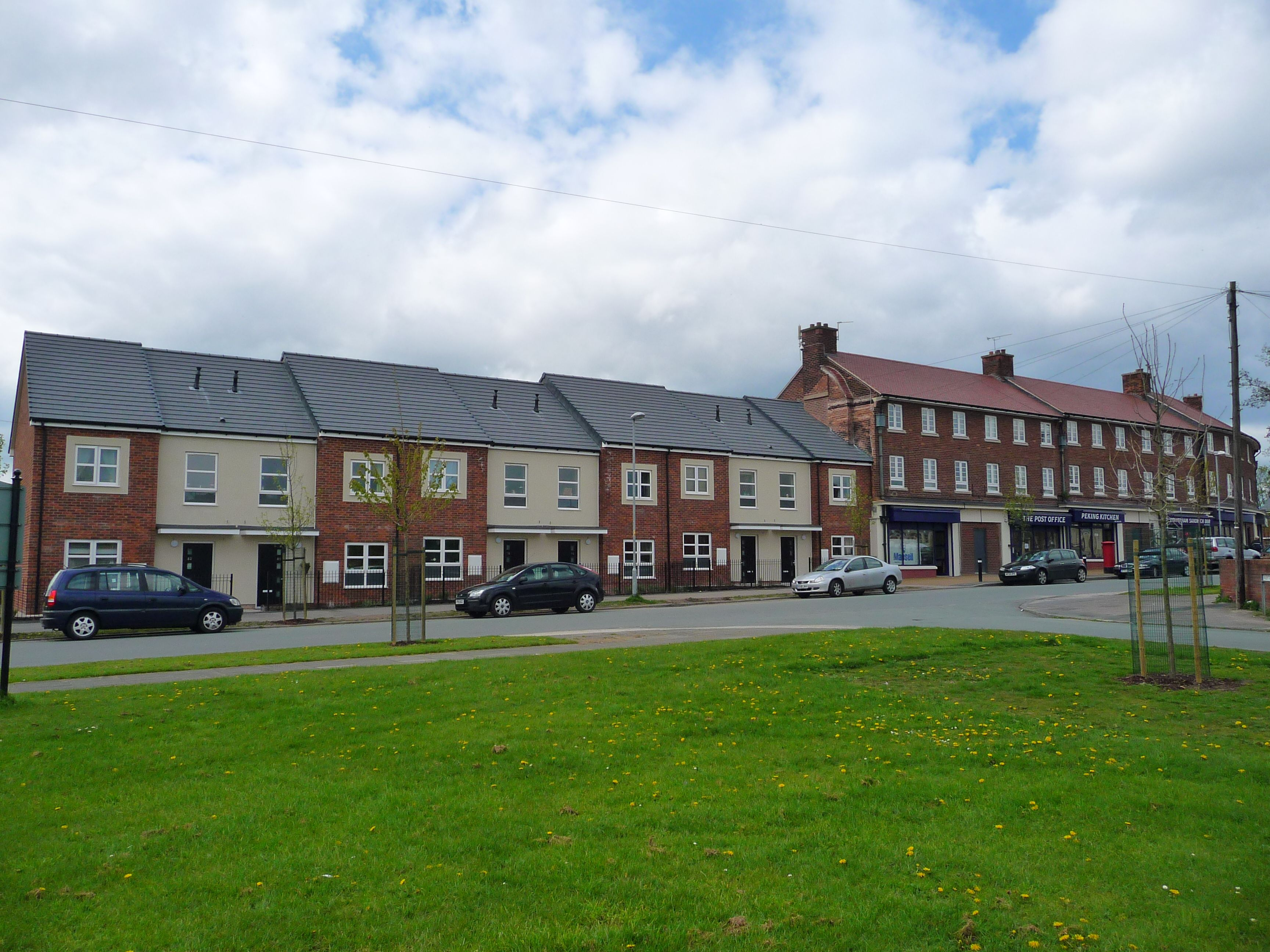 Milton Road, Ellesmere Port. Built on behalf of Muir Group Housing Association this scheme was a development of 29 new build houses and flats, refurbishment of 10 maisonette units and 10 retail units, and improvements to public realm. Croft Goode Architects.