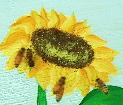 My honey bees flying around the sunflower painted on my beehive.