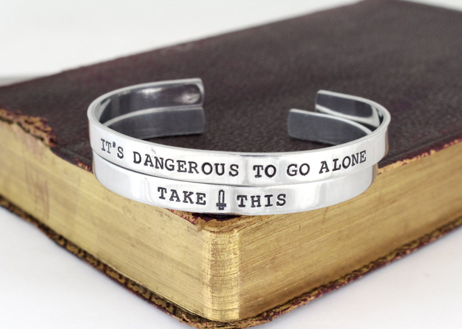 "This listing is for a set of 2 bracelets and is great for best friends or couples who want to show their bond. One bracelet reads ""It's Dangerous to go Alone"" and the other says ""Take This"" with a pix"