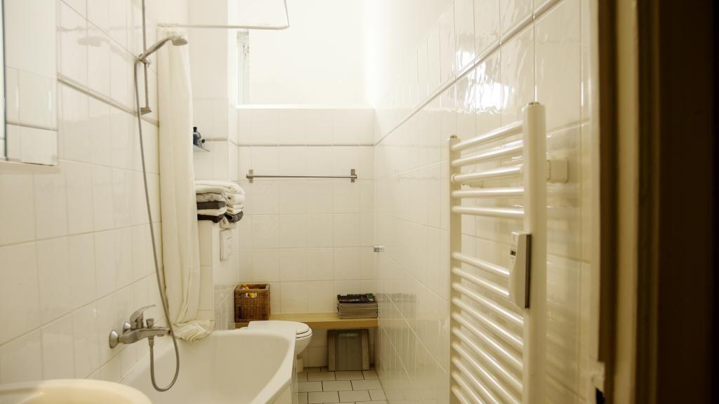 schönes berliner badezimmer mit hellen fliesen und heizung an der