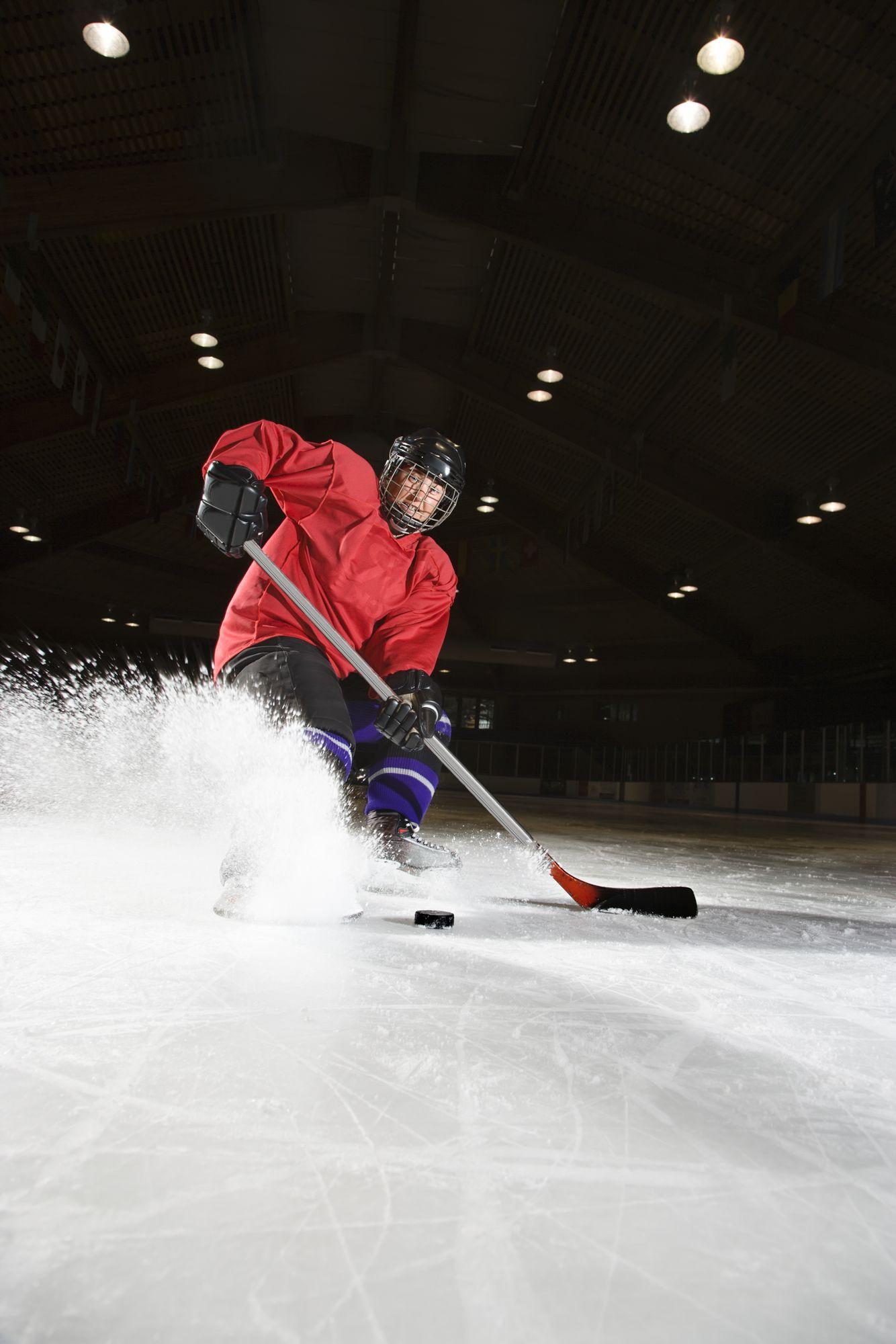 Caucasian woman hockey player sliding kicking up ice