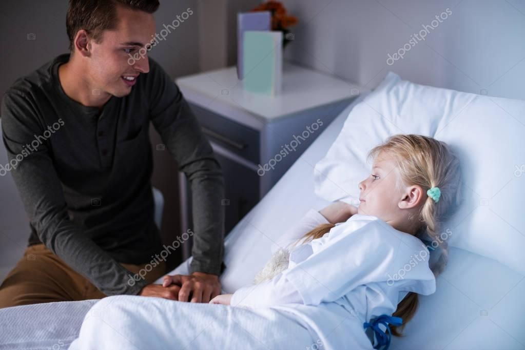 Father beside her daughter lying on hospital bed stock