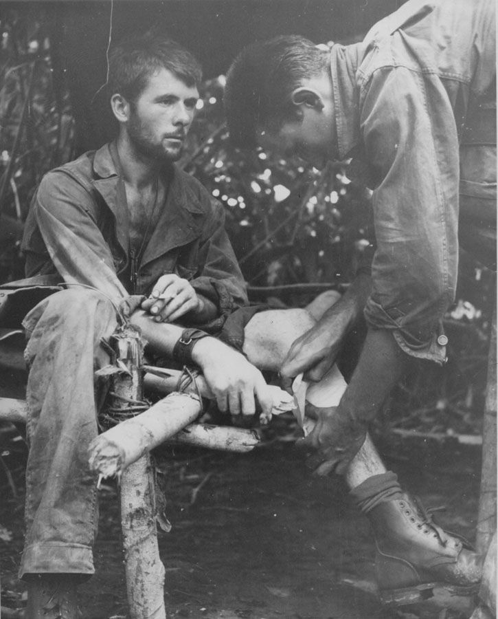 """""""'Wild Man' From Michigan Takes Jap Bullet Calmly – Described as a """"Wild Man"""" at the front and credited with killing between 30 and 40 japs as his unit cross New Guinea to trap the enemy in the Buna-Gona area, Private First Class Orin Sutton (left) of Charlevoix, Mich., sits calmly and has his leg bandaged after he was hit by a Jap machine gun bullet. He was back in action in less than 24 hours. Doing the bandaging is Private First Class Allie Poole of Petersburg, Mich."""" AP 12-15-42."""