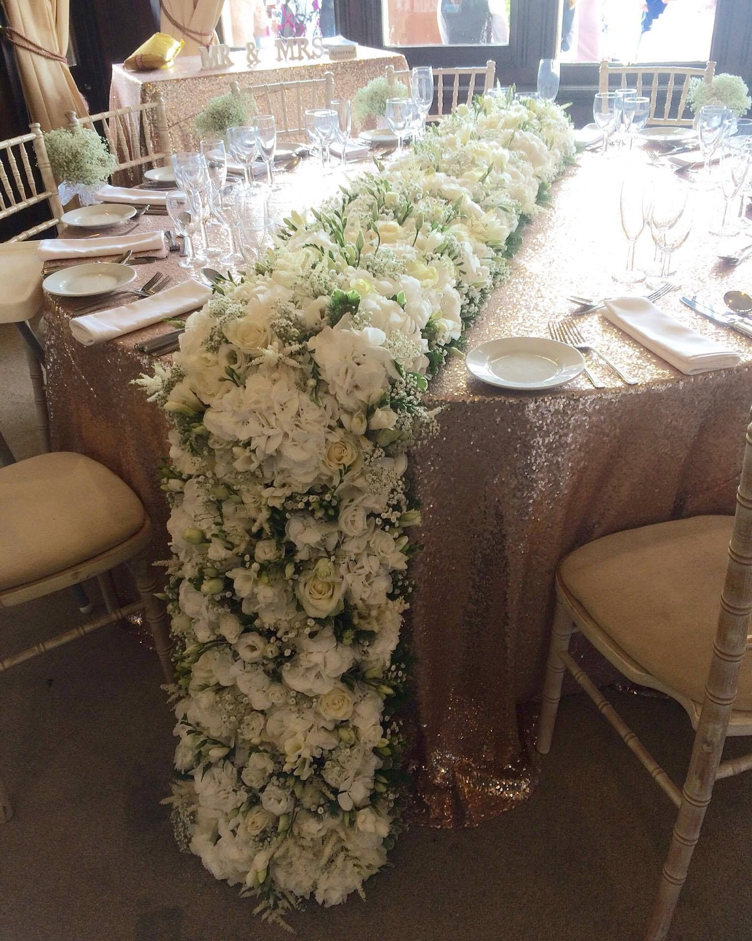 Floral Carpet Cascading Over And Down Off The Top Table White
