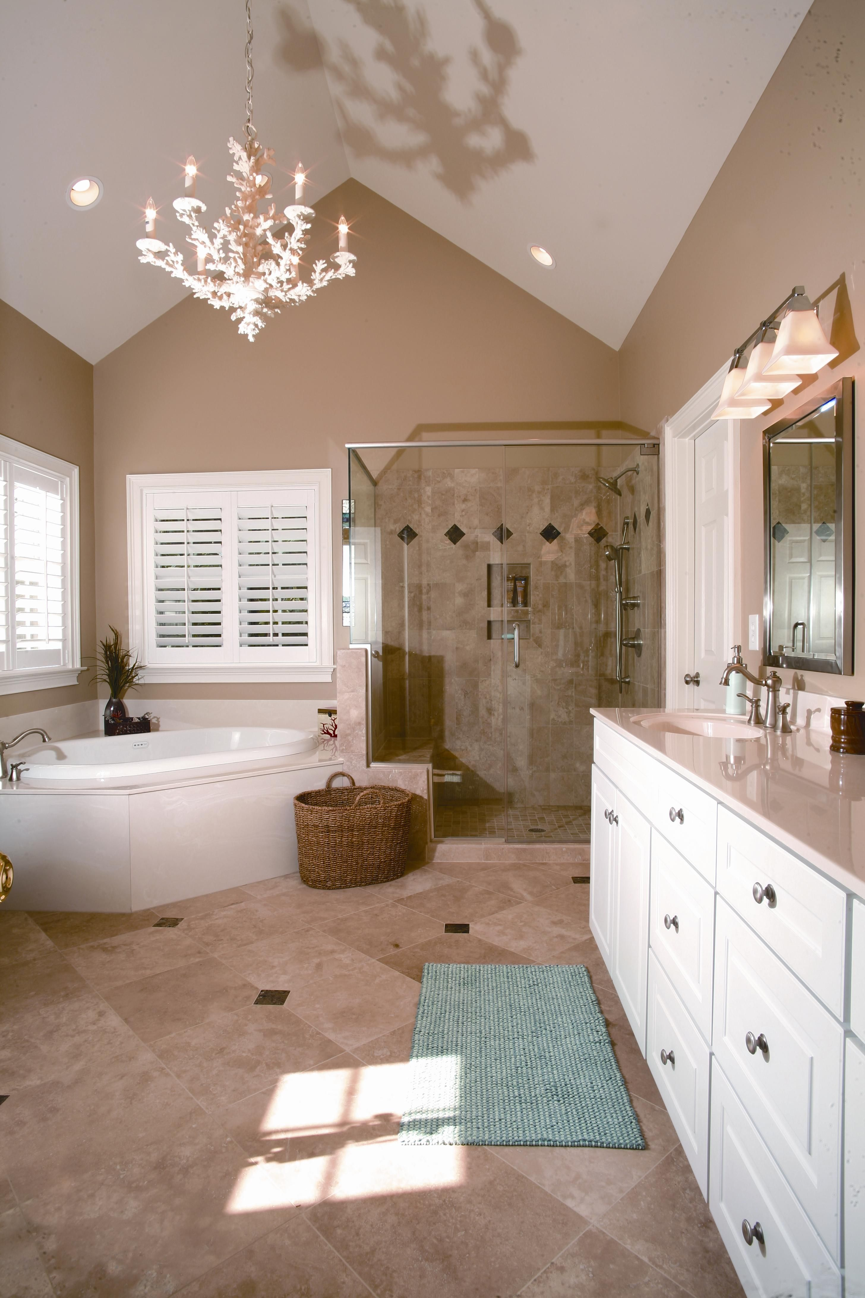 The vaulted ceilings makes the chandelier a perfect fit bathroom