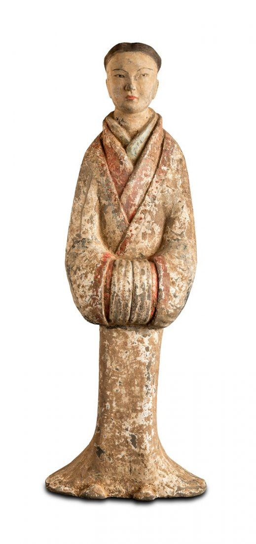 A large grey pottery court lady, Han Dynasty (206BC- 220AD) with original red white and black pigment her hand folded inside her sleeves, 44cm h