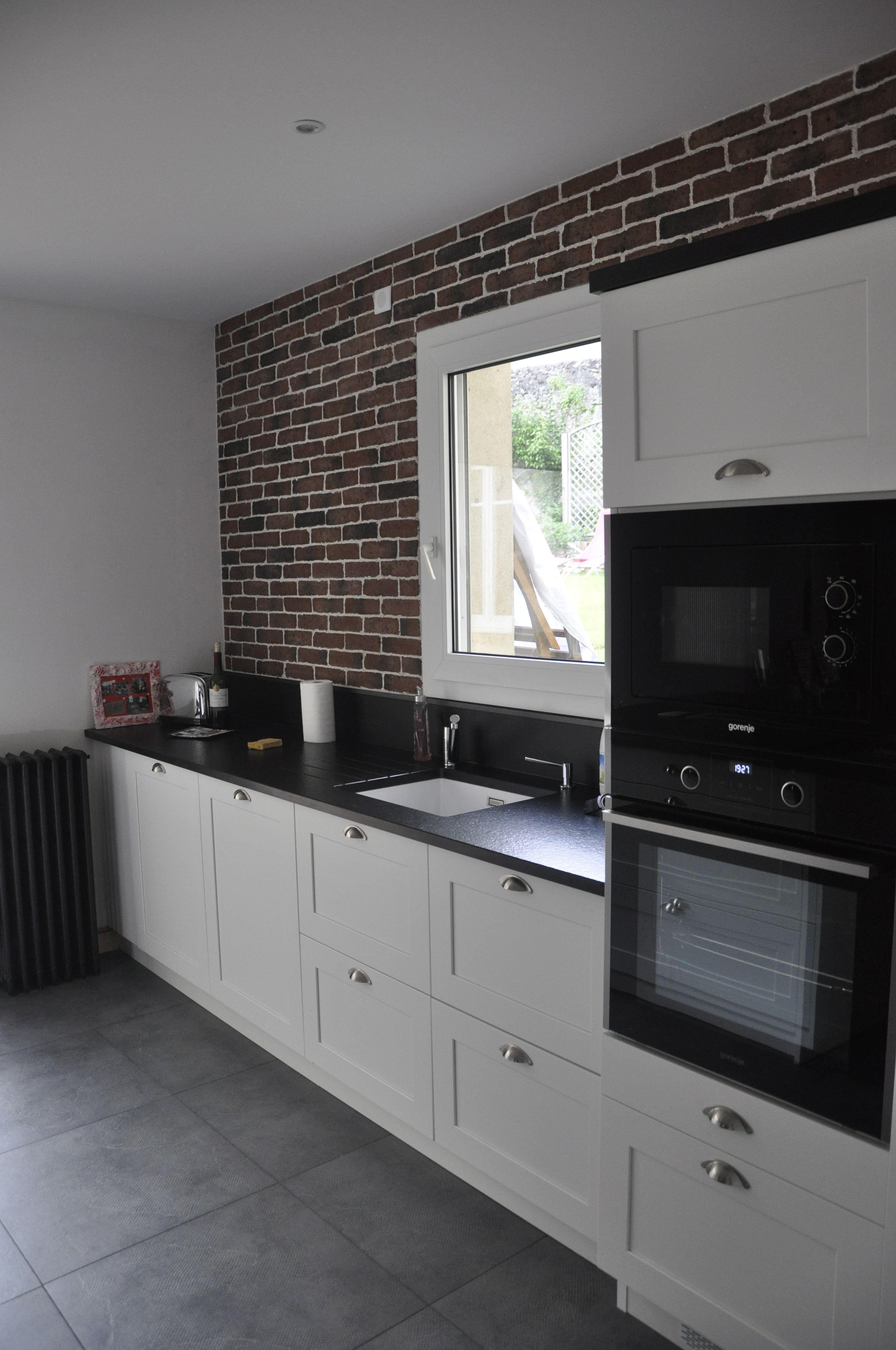 Hotte Sortant Du Plan De Travail cuisine blanche et granit noir sur mur brique style loft
