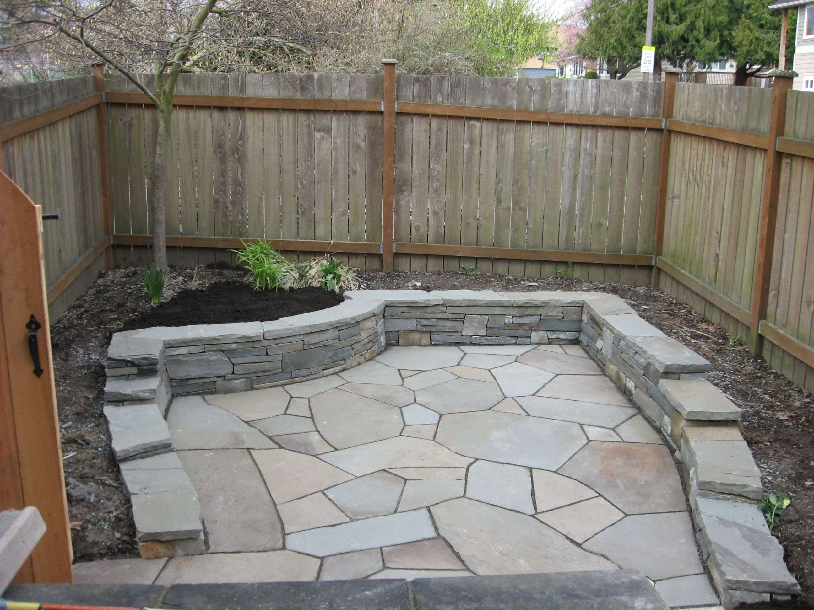 Flagstone patio with retaining wall yard pinterest for How to build a river rock patio