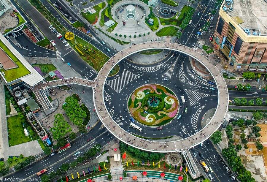 Zoomed view of a landmark architecture in Shanghai's Pudong the financial district. The circular walkway gives open access for pedestrians to all surrounding streets. As seen from above, standing at one of the observation decks in the Oriental Pearl Tower. Photo by Viktor Lcsaki