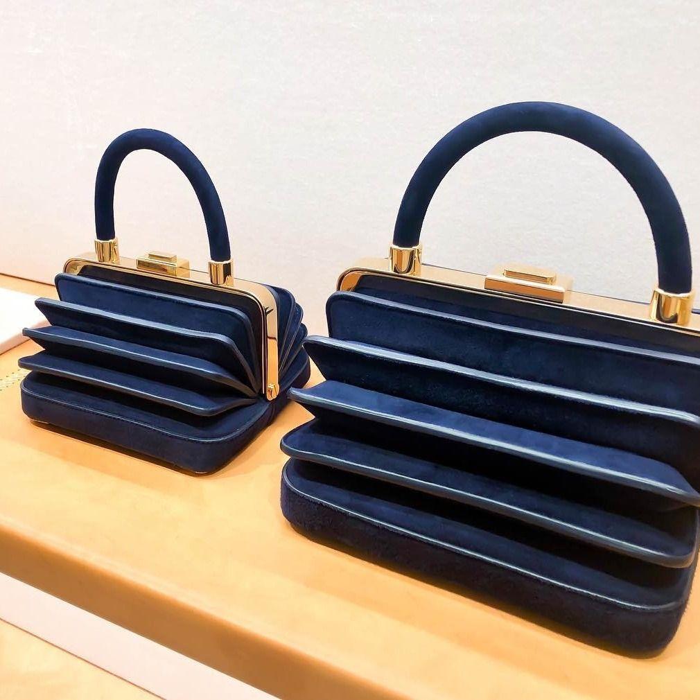 This blue suede top handle bag is magnifique