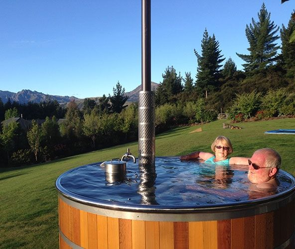 Couple Relaxing In A Stoked Hot Tub   Wood Fired Hot Tub   Stoked Stainless