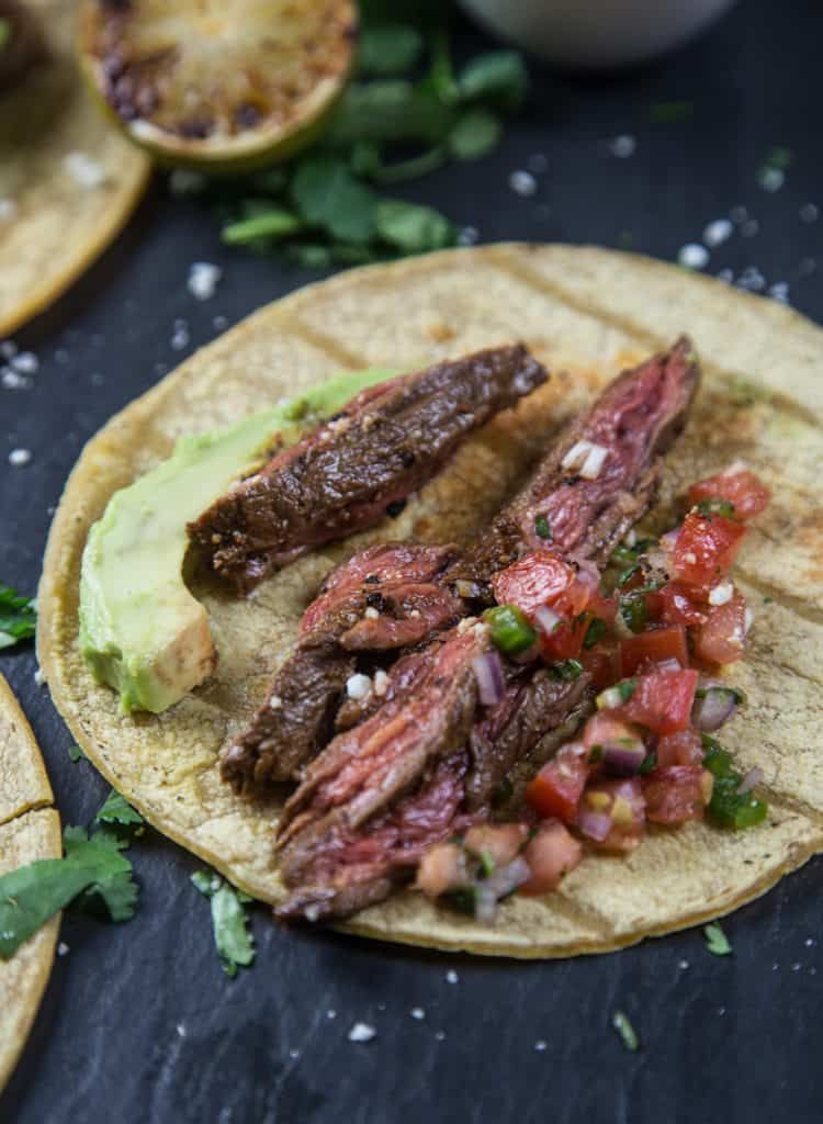 Carne Asada Steak Tacos #marinadeforskirtsteak Carne Asada Tacos with salsa and avocado, skirt steak on a grill, pinterest image width=600 height=1260 data-pin-description=Grilled Carne Asada Tacos made with marinaded skirt steak makes a great taco night! The skirt steak is grilled hot and fast and sliced thin for tender and flavorful steak tacos. Great marinade recipe, and complete how-to grill skirt steak. #tacos #carneasada #grilledcarneasada #skirtsteakrecipe #vindulge #asadatacos Carne Asad #marinadeforskirtsteak
