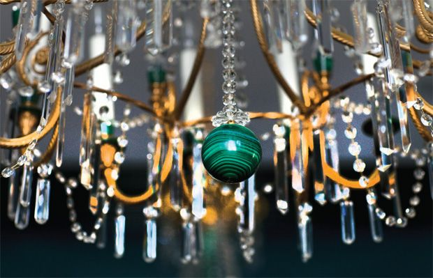 A semiprecious malachite weight dangles from one of a pair of custom crystal-and-malachite chandeliers.