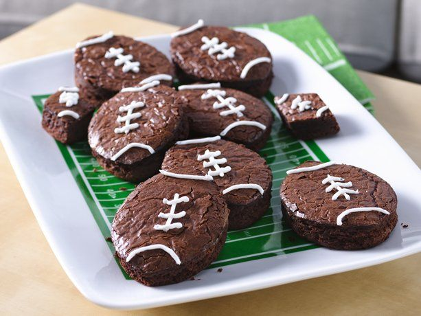 """You're sure to score many points with the football fans in your life once these football-shaped brownies hit the snack table. This creative game-day dessert is as easy as making boxed brownies—all you need is a football-shaped cutter (or a knife if you want to freestyle it) and some icing for the """"laces."""""""