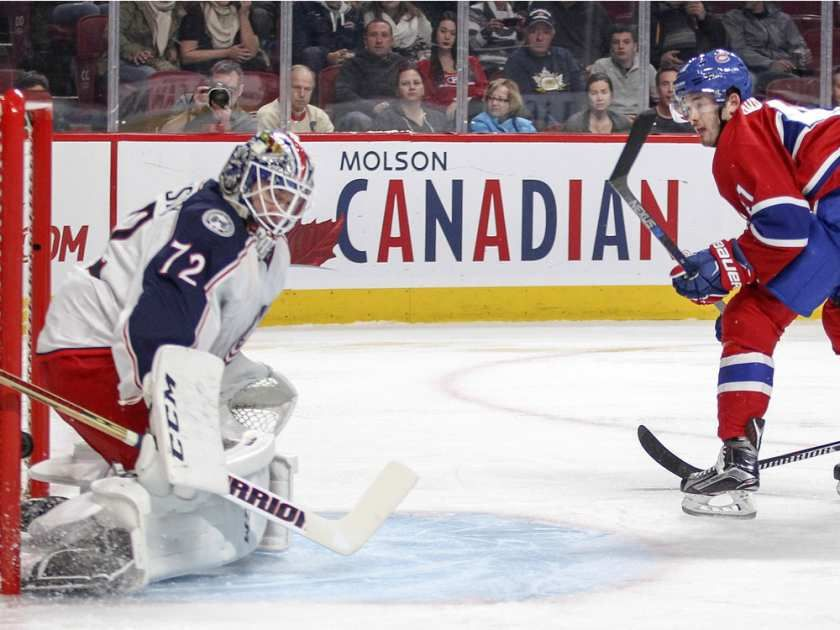 Montreal Canadiens Paul Byron shoots the puck past Columbus Blue Jackets goalie Sergei Bobrosvky for the first goal of the game despite backcheck by Jackets Kevin Connauton during first period of National Hockey League game in Montreal Tuesday December 1, 2015.