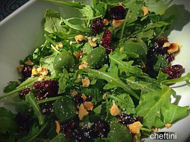 Arugula salad with Castelvetrano olives, crushed hazelnuts, craisins, and parmesan cheese with a splash of lemon juice.
